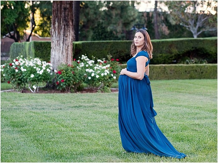 A woman in blue evening dress outdoors posing for a maternity photography session