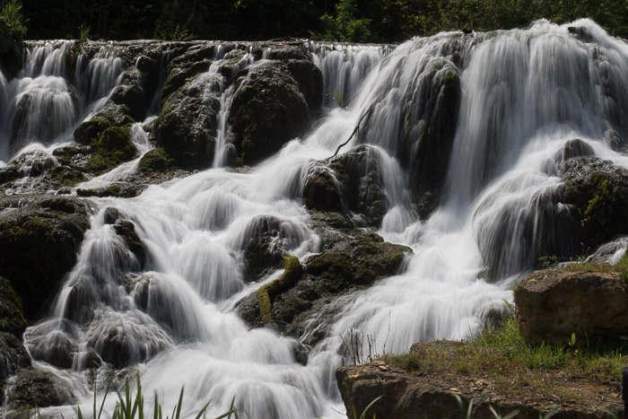 Beautiful flowing waterfall shot with long exposure to create motion blur with the water movement and imply fluidity.