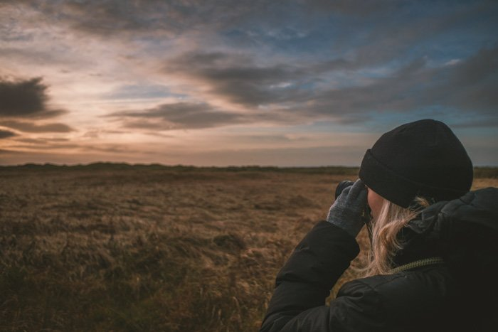 A nature photographer taking an evening landscape shot