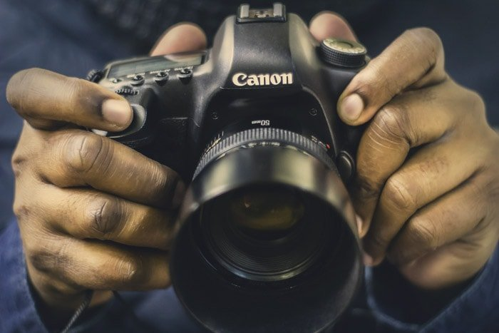 Close up of a man holding a Canon full frame DSLR fitted with a 50mm nifty fifty