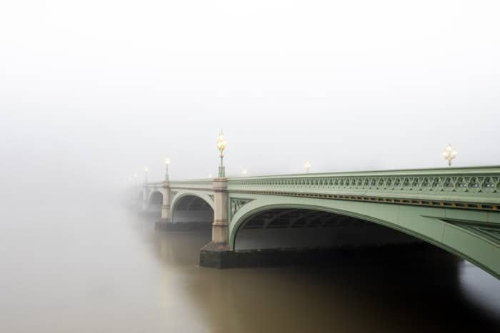 Atmospheric shot of a green bridge disappearing into fog