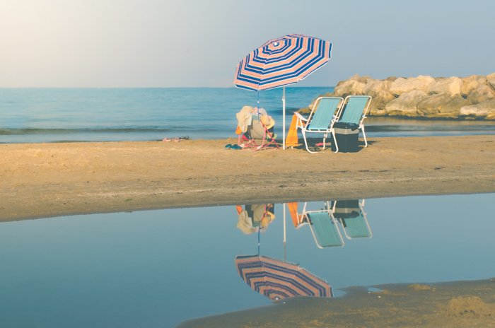 Serene beach photo of deckchairs and umbrella with the sea in the background