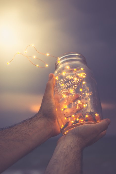 A person on a beach at night, holding a glass jar of fairy lights