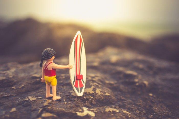 A playmobil character with a surfboard posed on a rocky beach, creative beach photography ideas.