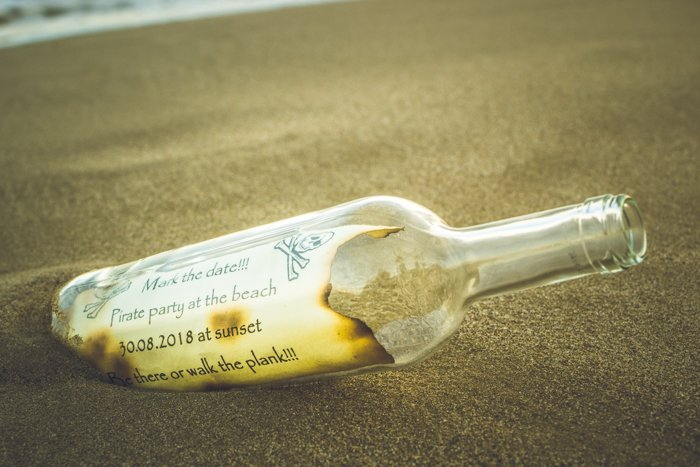 A pirate note inside a bottle in the sand - cool beach photography ideas