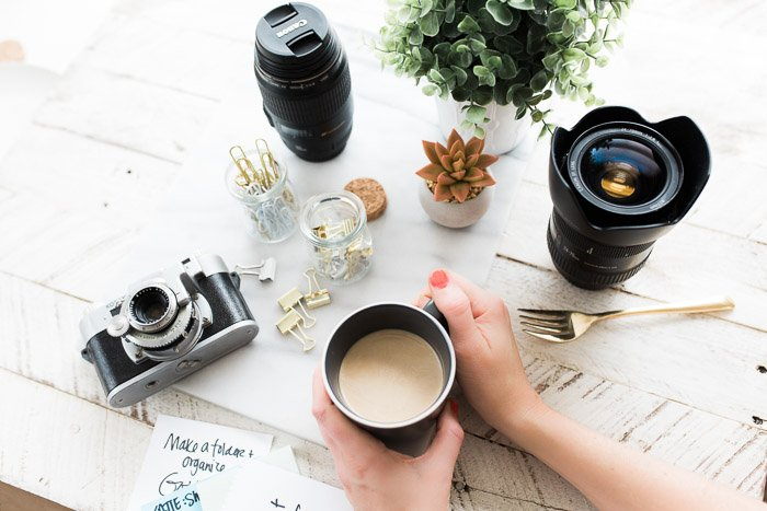 Overhead shot of photography equipment, accessories and coffee cup on a wooden table - camera insurance tips