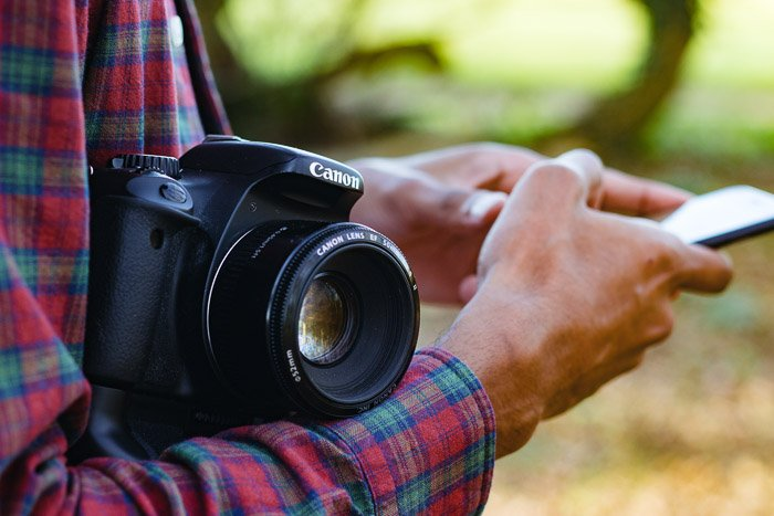 Close up shot of a man holding a DSLR and using his smartphone - why you need photography insurance and camera insurance