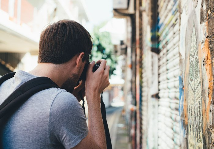 A man with DSLR camera taking photo of graffiti- photography laws by state