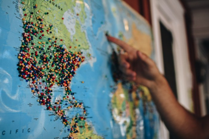 Close up of a hand pointing to a map of the world - street photography laws