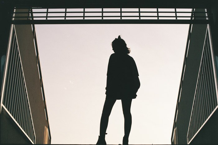 A silhouette of a girl standing in the middle of steel railings achieved through photography side lighting