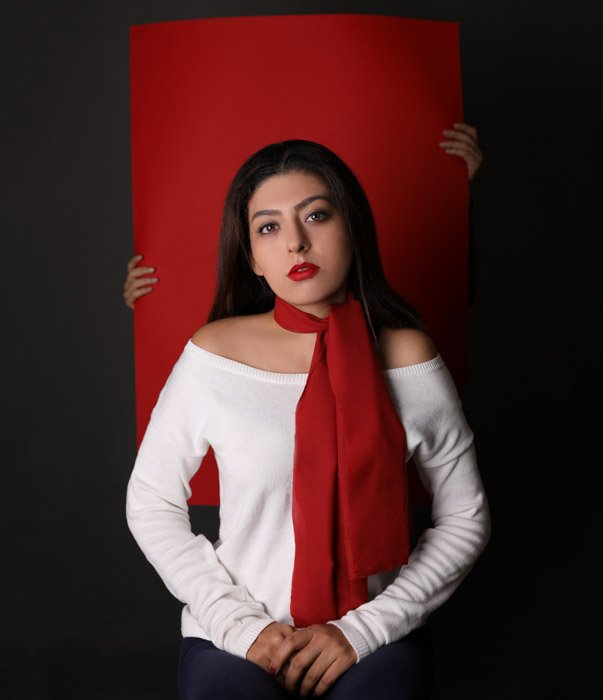 A studio portrait of a dark haired woman with someone holding a red portrait background behind her