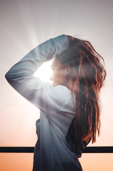 Atmospheric portrait of a dark haired woman against a sunset sky