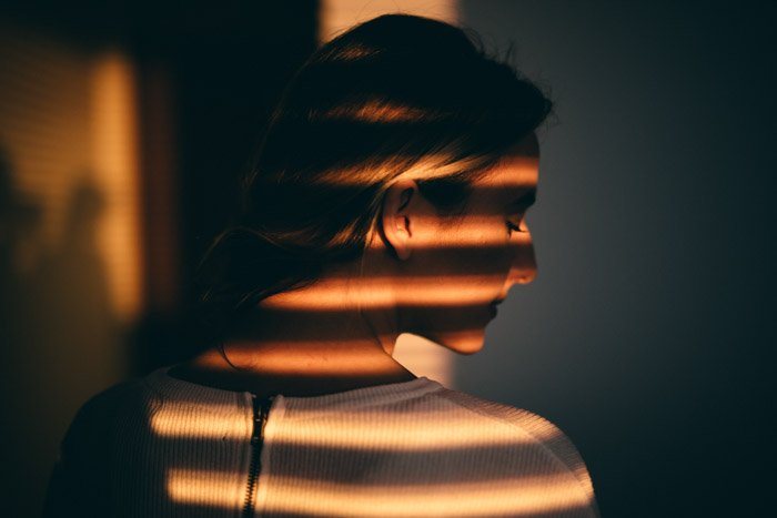 Moody chiaroscuro light portrait of a girl covered by striped shadows