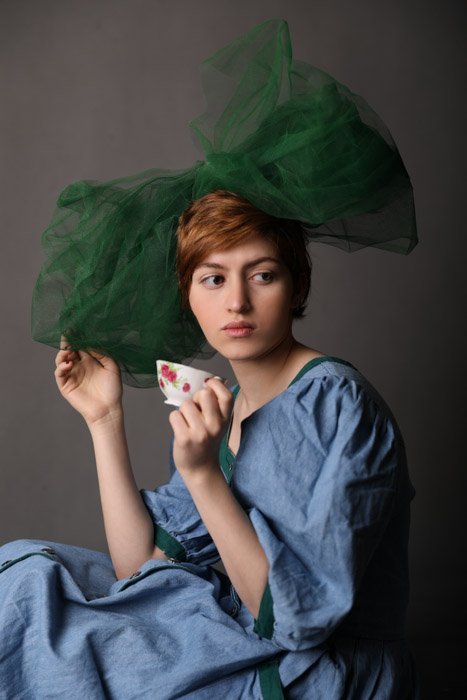 A studio portrait of a young woman posing with large green hair bow and a teacup against a grey background