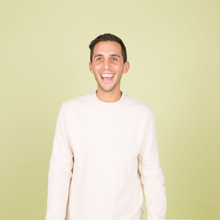 a playful of a young man in white shirt against a yellow background