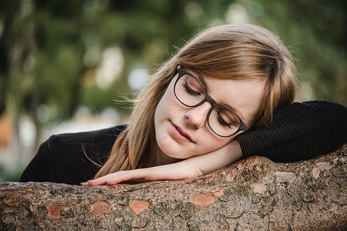 Portrait of a female model resting on a tree with a natural blurry portrait background