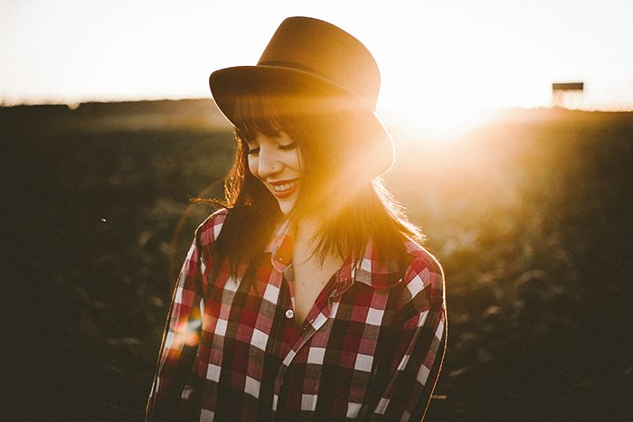 Portrait of a female model wearing a hat with the bright glare of the sun behind her serving as an interesting portrait background