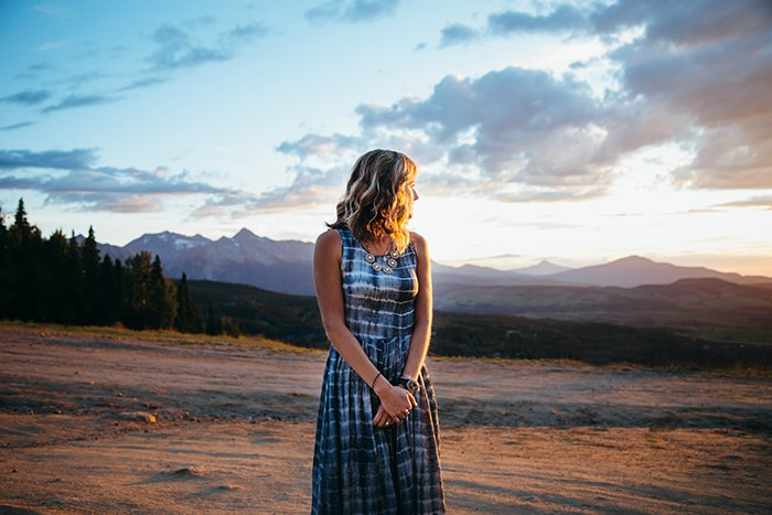 Portrait of a girl standing in front of a beautiful landscape