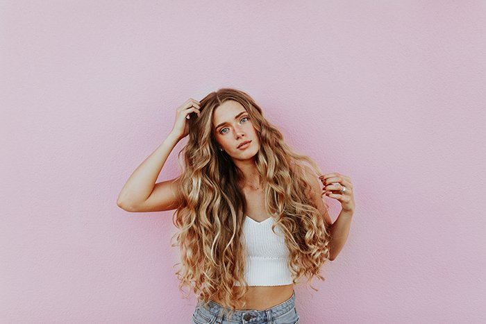 Portrait of a blonde girl posing in front of a pink portrait background