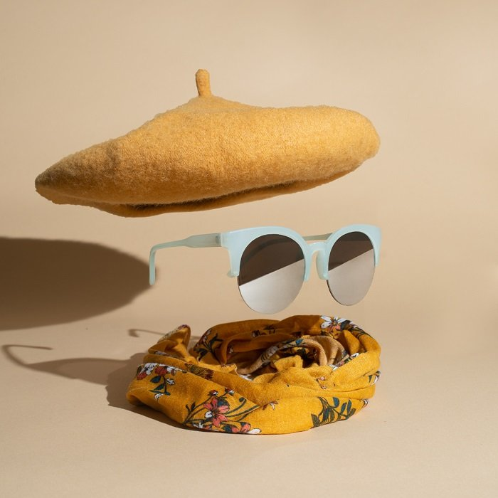 Cool product photography styling example of a levitating pair of sunglasses under a beret and over a scarf