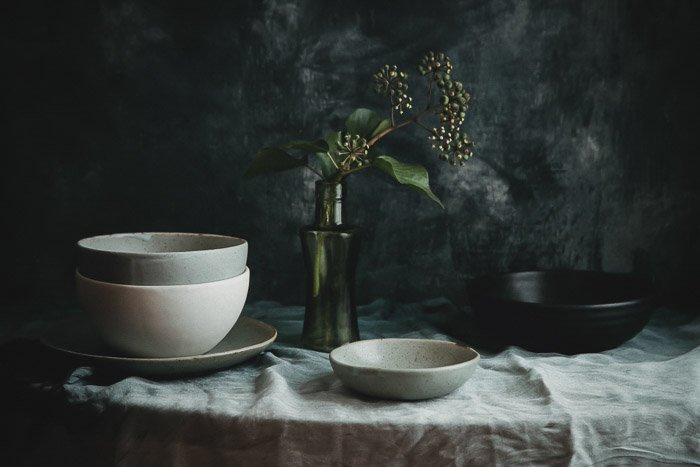 Still life of pottery bowls on a table against dark background - product photography tips