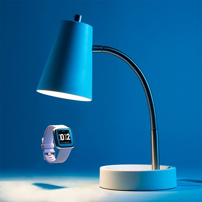 A floating watch under a blue lamp