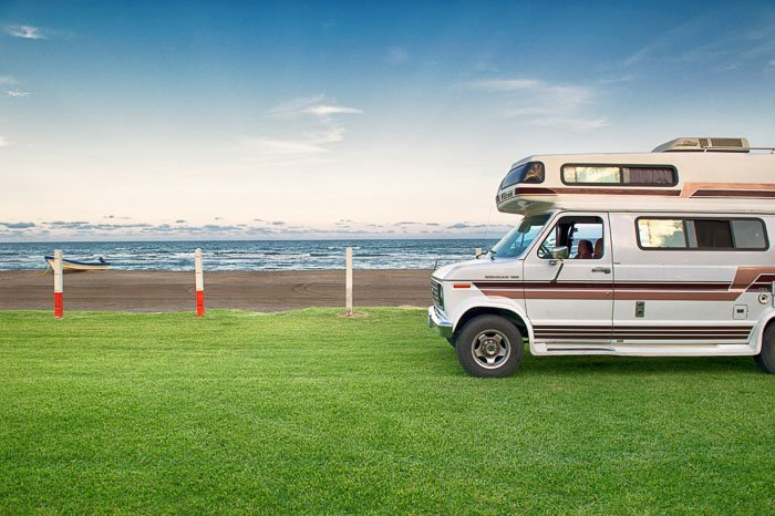 A camper van parked on grass with seascape behind