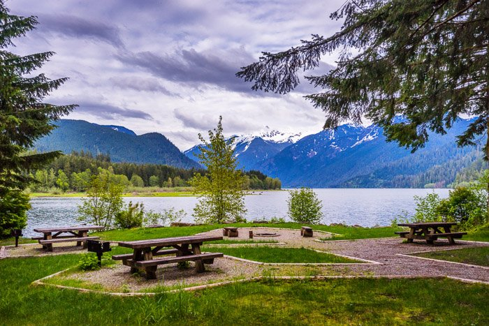 A campground picnic area with lake and mountains in the background