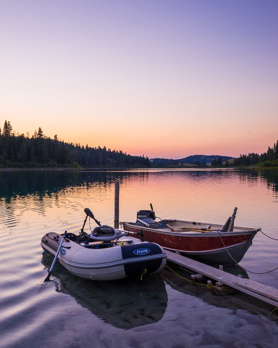 A road trip photography shot of two small boats tied up on a lake at evening