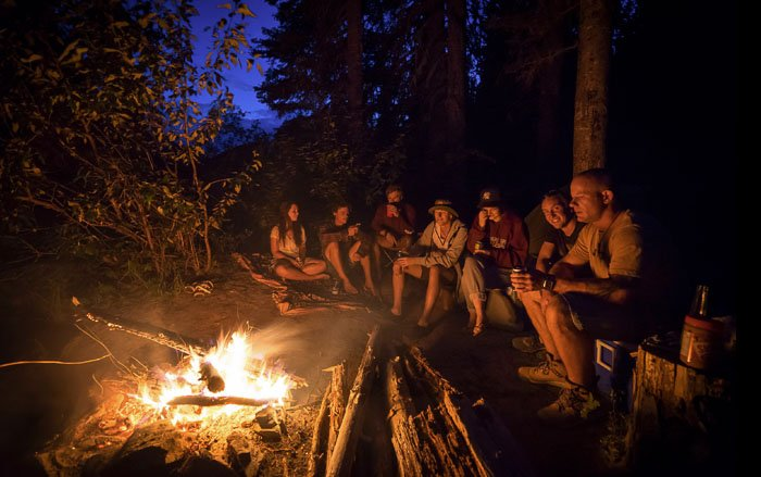 A group of people sitting around a campfire in a forest at night