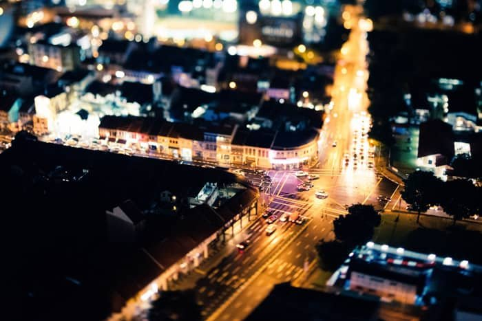 A sprawling cityscape at night, shot from overhead with a tilt-shift photography lens