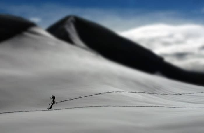 A person skiing down slopes with a snowy mountain behind, taken with a tilt-shift photography lens.