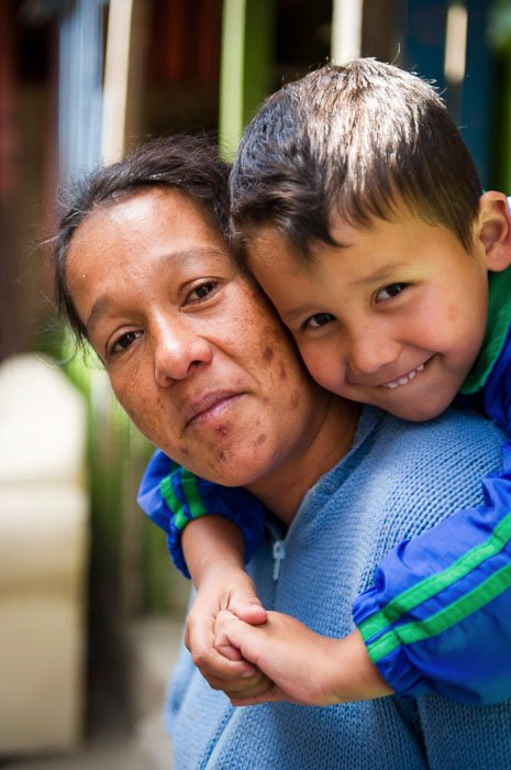 A close up portrait of a woman with a little boy on her shoulders taken by a travel photographer - should you tip for photos?