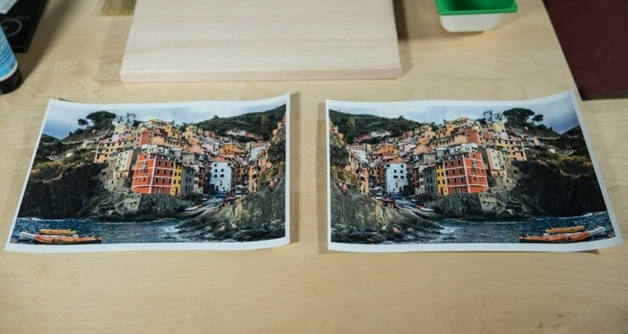 Two identical photos of a brightly colored coastal town, resting on a wooden board preparing to transfer photo to wood
