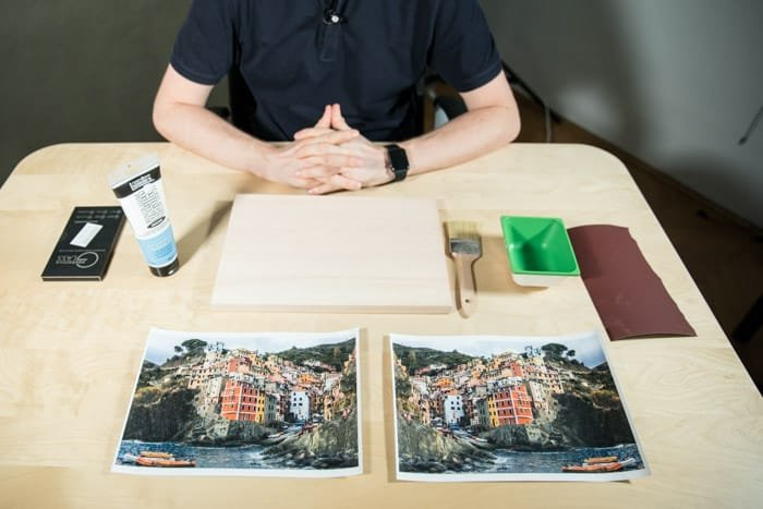 A man sits at a wooden table, before him is two identical photos of a brightly colored coastal town,glue, paintbrush, sandpaper and other materials to transfer laser print to wood