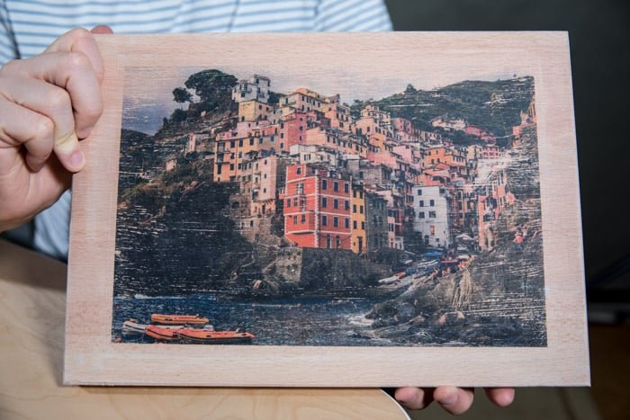 A man holding a wooden board with a colourful coastal town photo transferred to it
