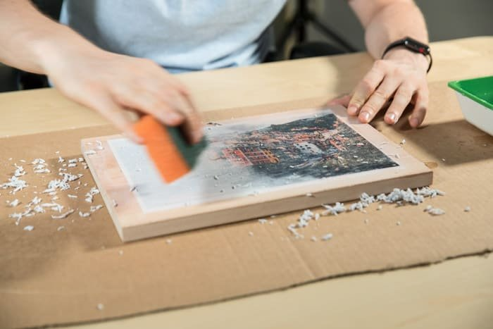 A man preparing a wooden board to transfer photos to wood