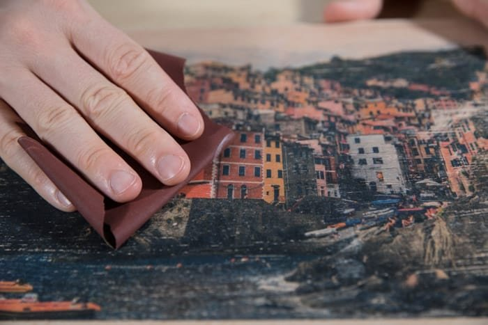 Close up of sanding the photo transfer on the wooden board - how to transfer laser print to wood