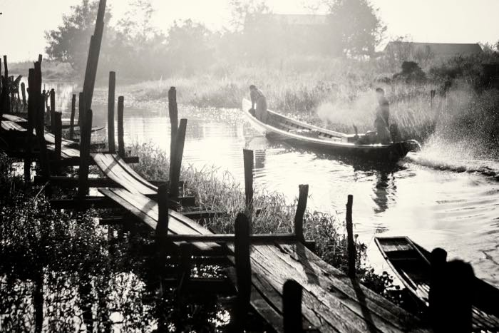 Striking monochrome travel images of a wooden bridge and small boat