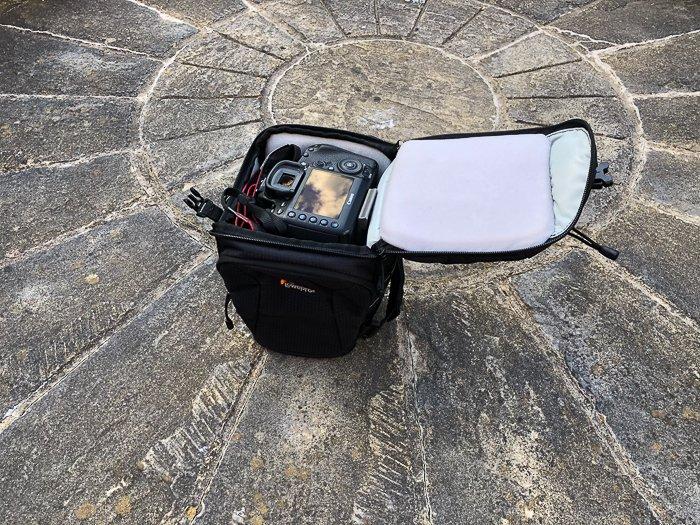 a toploader DSLR camera bag on stone ground