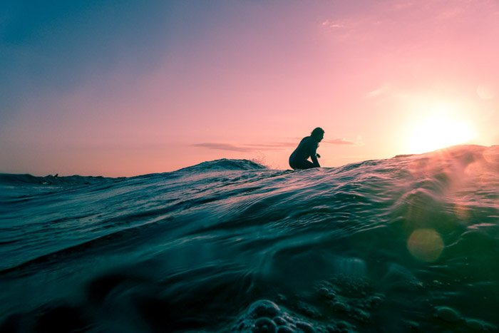 A dreamy adventure photography shot of a girl on the ocean at sunset