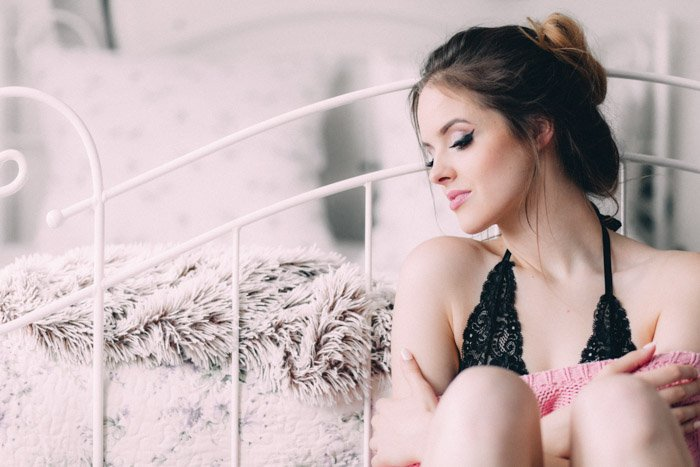 romantic boudoir photo of a girl sitting against a bed