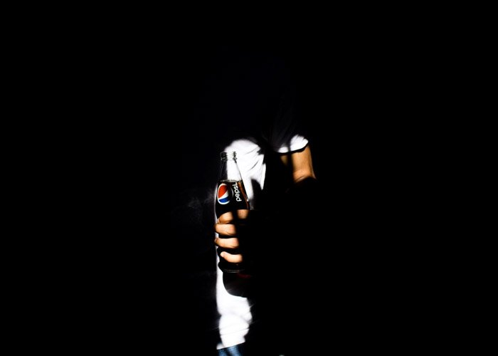shadowing commercial photo of a man holding a pepsi bottle