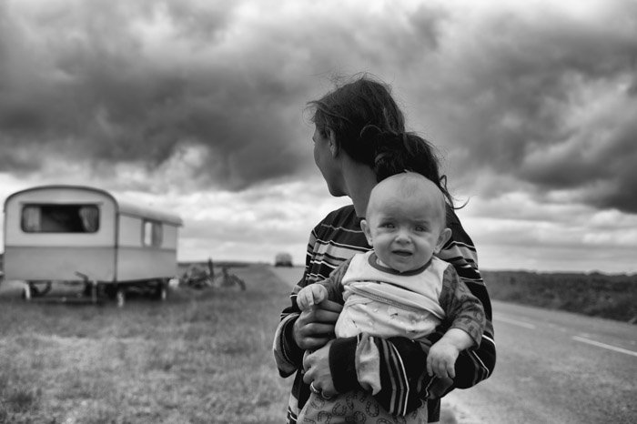 A woman holding a baby on a cloudy day