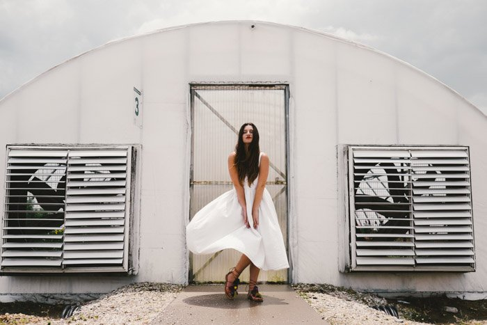 editorial fashion shoot of a model in a white dress posing outdoors