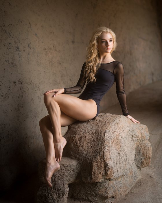 A girl posing elegantly on a rock formation