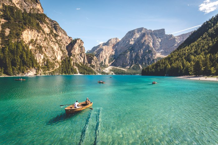 stunning shot of boats on a turquoise sea with a mountainous landscape behind