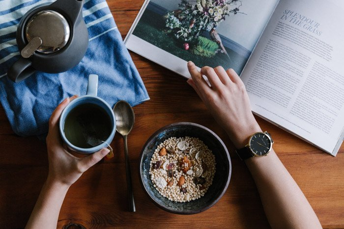 overhead shot of a person drinking tea and eating cereal while looking through a magazine