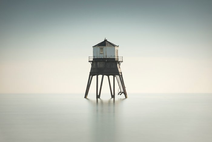 long exposure shot of a lonely looking tower on white water and against white sky