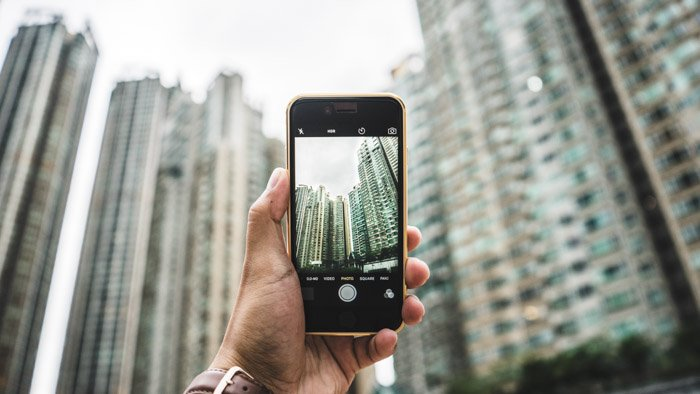 a person holding a smartphone to take photos of buildings